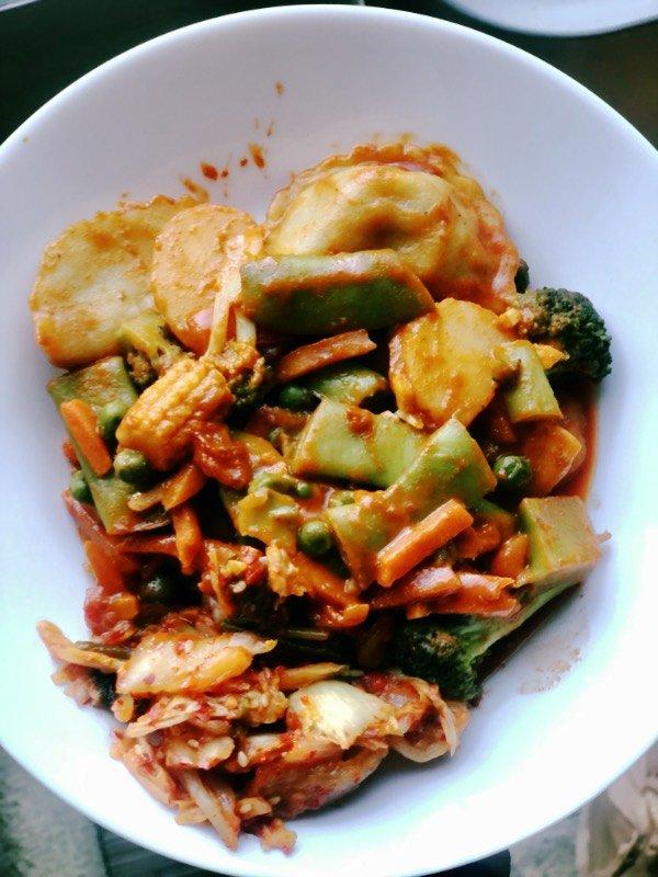 korean dumpling stir fry and kimchi in a white bowl.