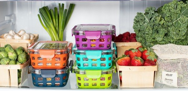 colorful meal prep container in refrigerator with fruits and vegetables.