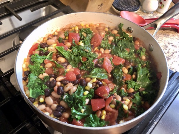 easy beans and greens in a pot on the stove cooking.