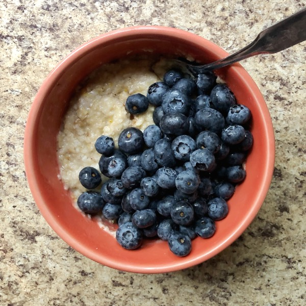 pink bowl full of oatmeal topped with lots of fresh blueberries.