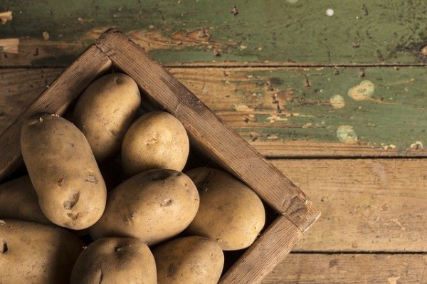 a box full of russet potatoes on a wooden table.