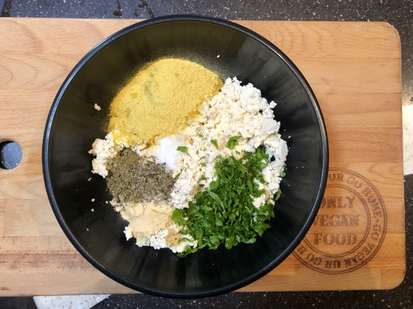 ingredients for tofu ricotta in a black bowl sitting on a wooden cutting board.
