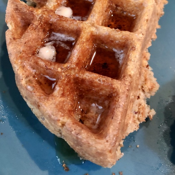 part of a vegan belgian waffle on a blue plate with vegan butter and maple syrup on top.